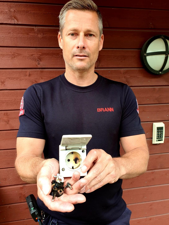 Brannformann Morten Nygaard viser frem stikkontakten som  begynte å brenne på utsiden av huset hans.