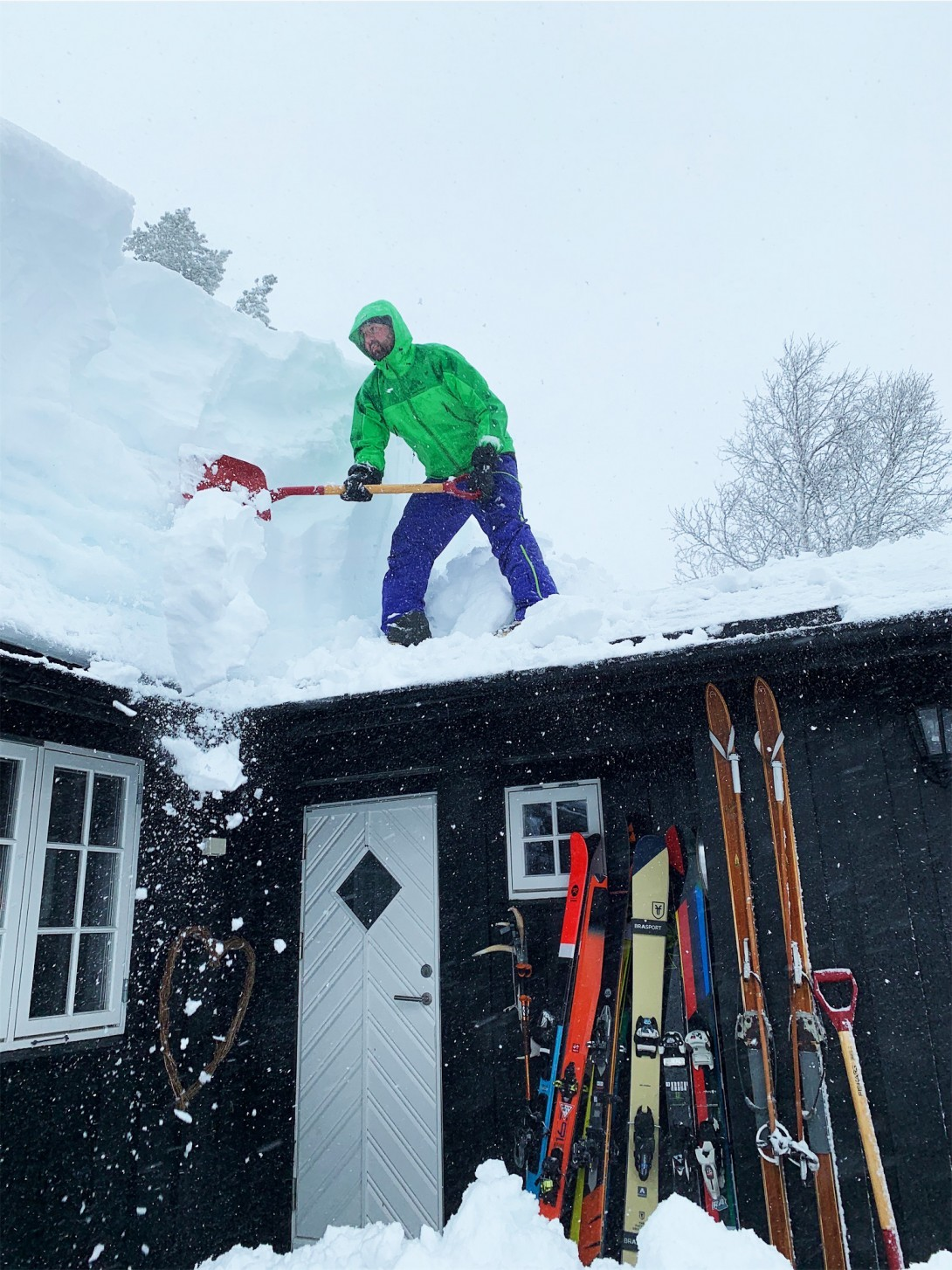 Sigbjørn Justnæs er i gang med å fjerne snø fra taket, han passer på at rømningsveien ikke blir blokkert.